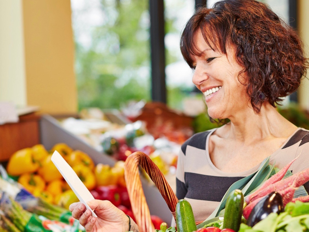 Smiling woman with shopping list buying fresh vegetables in a supermarket