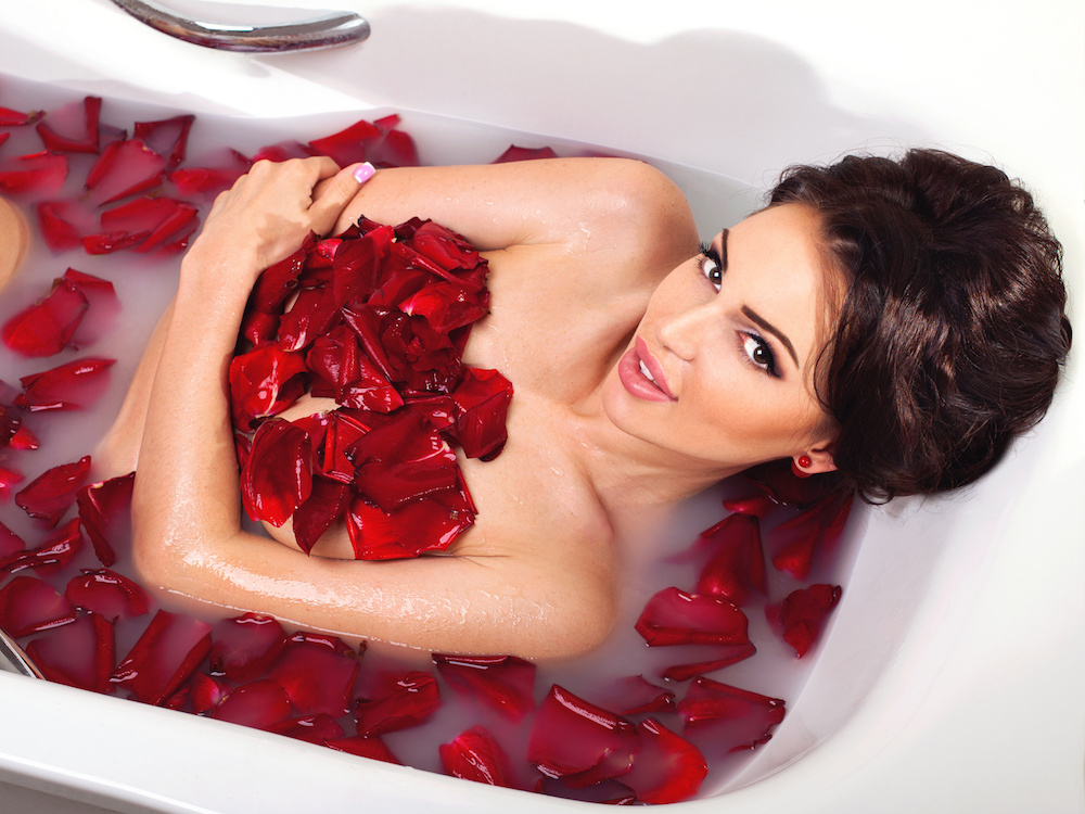 Sexy beautiful naked brunette woman laying in a bath with milk and red romantic rose petals. Luxury spa and body care