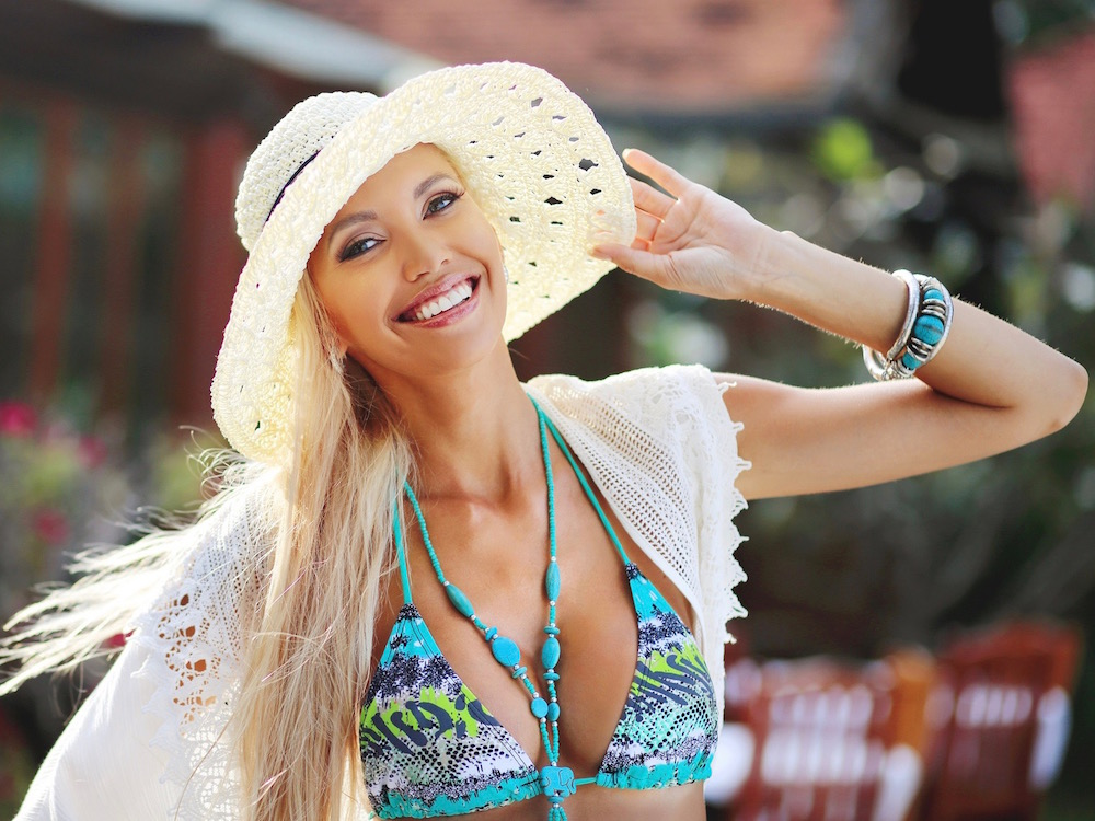 Pretty smiling blonde woman in hat having fun outdoor