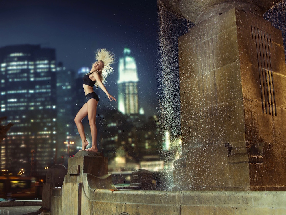 Athlete dancing on the fountain in the night